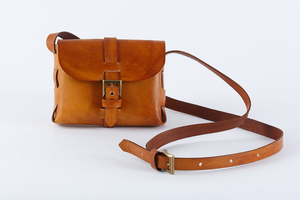 PLEASE NOTE THAT WE HAVE A 7 -14 DAY PRODUCTION LEAD TIME FORALL PRODUCTS, AS THEYARE MADE TO ORDER.    The Mini Sling Bag iscleverly folded without any stitching at all. It is a handymini bag, just big enough to safely hold your smallessentials.  Hand crafted usinglocally sourced vegetable tanned cow hide  Hand punched, hand cut  Embossed logo  Antique brass hardware  Buckle closure  Dimensions: H12cmx W 17cm x D 5cm  Please note thatIlundi products aremade with the finest quality materials available. Any irregularities in the colour or in the grain are normal characteristics of natural leather. Leather items may have wrinkles, scars or scratches that are an inherent quality and natural beauty of the hide.    SHIPPING:  South African orderssent withDawn Wing, 2-3 working days (over and above the production lead time). International orders sent via DHL. Fees automatically calculated at checkout.All customs fees to be paid by the receiver.