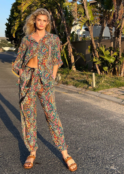 The paisley print pull onpant is flowing and loose in cut, high waisted withelasticated waist. Belt loops for the cord tie add a nice detail. The leg cut is straight and loosewith elasticated cuff (not tight) at ankle. Fabric has been pre-washed for shrinkage.  Cold wash /Machine washable cold only. Do not tumble dry