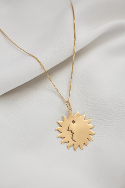 This pendant necklace features a stylish illustrated cut-out sun face design. 