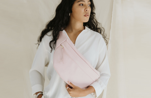 PLEASE NOTE THAT WE HAVE A 7 -14 DAY PRODUCTION LEAD TIME FORALL PRODUCTS, AS THEYARE MADE TO ORDER.    The Lunar in baby pink is made from locally sourced leather.  A fusion between a moon bag and a backpack, this minimal and sleek bag featuresan adjustable strap and canvas lining.  Can be worn across the front, across the back, or around the waist. Machine stitched.  Dimensions: H20cm x W58cm x D4cm (top)D1cm (bottom)  Size of pouch: 37cm x 20cm  Strap length at itswidest: 85cm (from end to end)    Ilundi products aremade with the finest quality materials available. Any irregularities in the colour or in the grain are normal characteristics of natural leather. Colour may naturally fade slightly with time and use. Leather items may have wrinkles, scars or scratches, that are an inherent quality and natural beauty of the hide.    SHIPPING:  South African orderssent withDawn Wing, 2-3 working days (over and above the production lead time). International orders sent via DHL. Fees automatically calculated at checkout.All customs fees to be paid by the receiver.