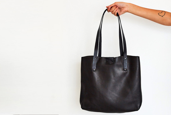PLEASE NOTE THAT WE HAVE A 7 -14 DAY PRODUCTION LEAD TIME FORALL PRODUCTS, AS THEYARE MADE TO ORDER.    TheSoft Tote bag in black game skin is entirelyhand stitched. Features apress stud closure and a hand stitched leatherinside pocket.  Hand crafted usinglocally sourced game skin and hand dyed vegetable tanned cow hide.  Hand stitched and hand cut  Embossed logo  Dimensions: H32cm x W 40cm x D 6cm  Please note thatIlundi products aremade with the finest quality materials available. Any irregularities in the colour or in the grain are normal characteristics of natural leather. Colour may naturally fade slightly with time and use. Leather items may have wrinkles, scars or scratches, that are an inherent quality and natural beauty of the hide.    SHIPPING:  South African orderssent withDawn Wing, 2-3 working days (over and above the production lead time). International orders sent via DHL. Fees automatically calculated at checkout.All customs fees to be paid by the receiver.