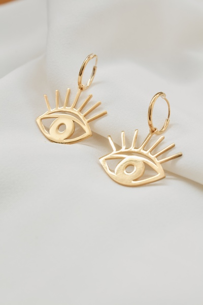 Beauty is in the eye of the beholder & thesegoldeneyes arethewindow to thesoul  Material:  - Made in brass andgold plated.  - Hoop is sterling silver  - Hoop size: 10mm  - Pendant size: 2cm wide    Shipping:  Each piece is made to order, the production time after your order takes around 3 days before shipping.  Shipping takes 5 days with international and 3 days local couriers.    - Earrings are sold as a pair or as singles  All our jewellery is handmade in our Cape Town studio.  All our jewellery is nickelfree.