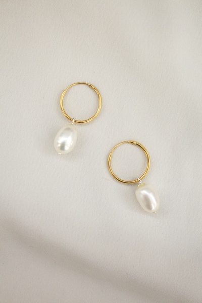 A lightweight hoop earring with suspended freshwater pearl.  - Earrings come as a pair  - Hoop Size: 15mm diameter  - Lightweight freshwater pearls  - Gold plated option with sterling silver base  All our jewelry is nickel free.